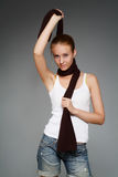 Girl with a scarf. The young woman with a brown scarf on a grey background stock photos