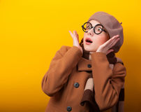 Girl in scarf and coat. Redhead girl in coat and scarf on yellow background Stock Image