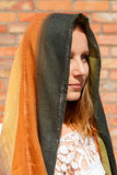 Girl with scarf covering the head. On a brick background Royalty Free Stock Photography