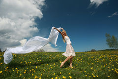 Girl with scarf in dandelion field Stock Images