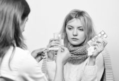 Girl in scarf examined by doctor. Cold and flu remedies. Doctor communicate with patient recommend treatment. Doctor ask. Patient about symptoms. Flu and cold royalty free stock photo