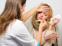 Girl in scarf examined by doctor. Cold and flu remedies. Woman consult with doctor. Doctor communicate with patient. Recommend treatment. Doctor ask patient royalty free stock image