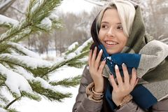Girl in a scarf and a fashionable winter multi-colored manicure. Next to a pine close-up.Nail art royalty free stock photo