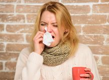 Girl in scarf hold tea mug and tissue. Runny nose and other symptoms of cold. Tips how to get rid of cold. Cold and flu. Remedies. Remedies should help beat royalty free stock image