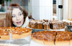 Girl in scarf looking at the bakery showcase. Woman in scarf looking at the bakery glass case full of different pieces of cakes Stock Images