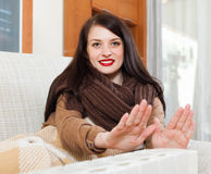 Girl in scarf  warming near warm heater Royalty Free Stock Photography