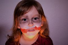 A girl with a scarred face. Face on the style of the joker.  stock images