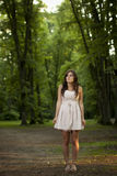 Girl in scary forest. Young girl at dusk in scary forest. Moody horror concept Stock Images
