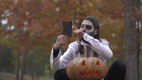 Halloween. Girl with a scary Halloween make-up is sitting with a butcher`s knife. Girl with a scary Halloween make-up is sitting with a butcher`s knife stock footage