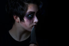Girl in scary makeup with combat knife on black background Stock Photo