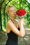 Girl scenting bouquet. Beautiful blond girl scenting bouquet of red roses Stock Images