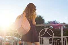 Girl with school backpack in uniform standing with her back. Back to school, child looks forward royalty free stock image