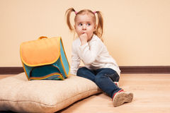 Girl with a School Bag. Little girl sitting with a finger in her mouth on a floor with a big school bag near by, horizontal studio shot royalty free stock photos