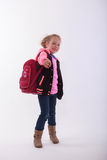 Girl with school bag points with the finger in the camera Stock Images