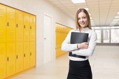 Girl in school corridor. Girl standing in school corridor holding black folder. Concept of high school education. 3d rendering Royalty Free Stock Photo