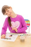 Girl school girl draws paints and brush on a piece Royalty Free Stock Photo