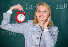 Girl school lecturer. Welcome teacher school year. Health and daily regime. Educator start lesson. She cares about. Discipline. Woman teacher hold alarm clock stock images