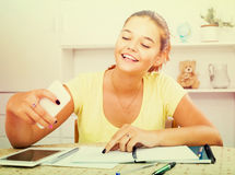 Girl school pupil taking self portrait on smartphone while study. Young happy russian  girl school pupil taking self portrait on smartphone while studying Stock Image