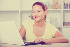 Girl school pupil typing on laptop while studying indoors Royalty Free Stock Image