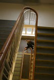 Girl in school staircase. A schoolgirl walking up a staircase in an old schoolbuilding Royalty Free Stock Images