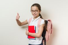 Girl school student, with a backpack and notebooks showing thumbs up sign, background bright wall in school stock image
