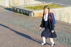 Girl in school uniform with a backpack rises a ladder. Girl in school uniform with backpack rises a ladder royalty free stock photography