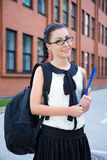 Girl in school uniform with backpack standing in campus Stock Photo
