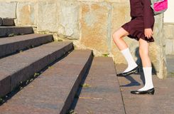Girl in school uniform with a backpack walking on steps. Girl in school uniform with backpack walking on steps stock image