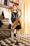 Girl in school uniform dress holds alto saxophone Stock Photos