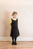 Girl (4) in school uniform pinafore Royalty Free Stock Photo