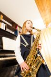 Girl in school uniform playing on alto saxophone Stock Photo