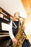 Girl in school uniform playing on alto saxophone Stock Photo