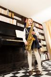 Girl in school uniform plays on alto saxophone Stock Photos