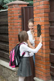 Girl in school uniform ringing in doorbell and mother opening th Royalty Free Stock Photo