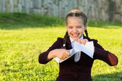 Girl in school uniform sits on grass and rips a piece of paper royalty free stock images