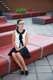 Girl in school uniform sitting on bench Stock Photo