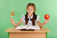 Girl in a school uniform sitting at the desk and choose candy or an apple Royalty Free Stock Photos