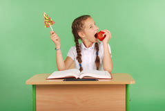 Girl in a school uniform sitting at the desk and choose candy or an apple Royalty Free Stock Photo
