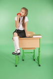 Girl in a school uniform sitting on desk and eat apple. Isolated on green Stock Photo