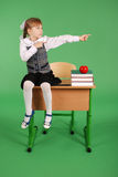 Girl in school uniform sitting on the desk Stock Photography