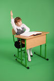 Girl in a school uniform sitting at a desk Royalty Free Stock Image
