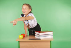 Girl in a school uniform sitting at a desk and points. Isolated on green Stock Photos