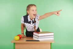 Girl in a school uniform sitting at a desk and points. Isolated on green Royalty Free Stock Photos