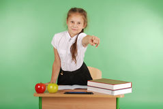 Girl in a school uniform sitting at a desk and points. Isolated on green Stock Photography