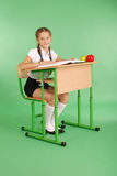 Girl in a school uniform sitting at a desk and reading a book. Isolated on green Royalty Free Stock Photo