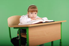 Girl in a school uniform sitting at a desk and reading a book Stock Photos