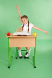 Girl in a school uniform sitting at a desk and stretches Stock Photos