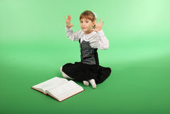 Girl in a school uniform sitting in front of an open book Royalty Free Stock Photos