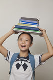 Girl in school uniform smiling and holding bunch of notebooks and laptop on her head, Studio shot Stock Image