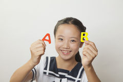Girl in school uniform smiling and holding plastic letters, Studio shot Stock Images
